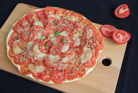 photo d'une tarte à la tomate très simple à faire avec des enfants présenté sur un fond noir