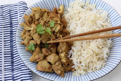 photo d'une assiette de poulet au curry et sauce soja avec des feuilles de coriandre fraîches